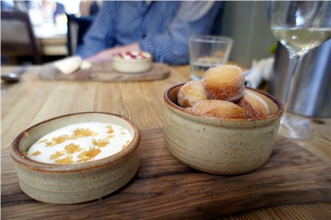 Bowl of warm rhubarb jam doughnuts with ginger sugar and sour cream